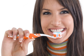 A woman holding a toothbrush ready to brush her teeth