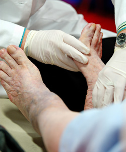 Photo: A podiatrist examining the injured feet of an elderly person