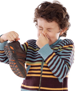 A child holding a shoe pinching his nose and making a bad smell face