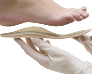 A podiatrist fitting a foot with an orthotic